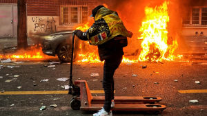 Man på en handstaplare åker på en gata där det brinner vid trottoarerna.