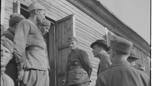 Män står utanför en dörr på det tyska fånglägret på Tulludden i Hangö.