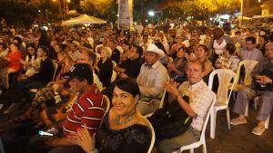 Många människor sitter och applåder<ar på poesifestival i Lantiamerika. Kvinna ser in i kameran