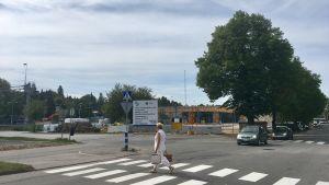 Vy över ett järnvägsbrobygge. Bilar kör på gatan framför och en fotgängare går över ett övergångsställe.