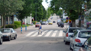 Några personer går över ett övergångsställe vid en väg där många bilar har parkerat.