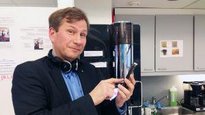 Reidar Wasenius med mobiltelefon vid kaffeautomat
