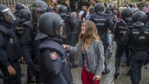 En kvinna talar med polisen utanför en skola i L'Hospitalet Llobregat i Barcelona.