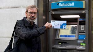"""Joaquim Curbet deltog i protesten på fredag och visar upp ett kuvert med de 155 euro som han lyfte från Banc Sabadell i Barcelona. Han sade sig hoppas att protesten """"ökar trycket mot den spanska regeringen""""."""