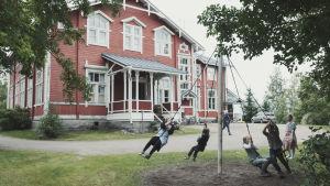 Suuri punainen koulurakennus valkoisine ikkunanpuitteineen. Etualalla pihalla lapset pyörivät narujen varassa tolppaa ympäri.