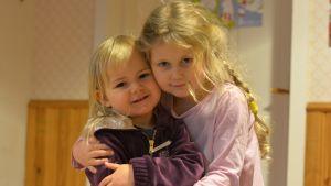 Betsy och Saga kramar om varandra på daghemmet Prästkragen i Prästkulla.