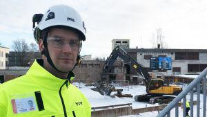 Projektledare Juha Pöntinen framför grävmaskinen som river Valkolinna.