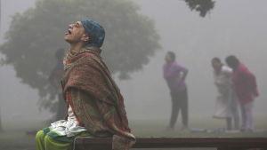 En kvinna utövar yoga i ett luftförorenad New Delhi.