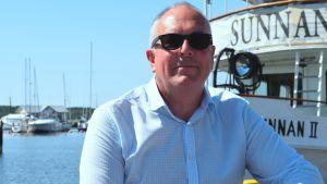Företagare Tom Nylund framifrån sittande på en brygga vid restaurangbåten Sunnan en solig sommardag. Hav i bakgrunden.