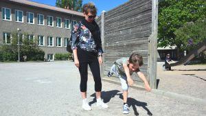 Mamma Åsa Olin med sonen Milos Christides ute på Seminariskolans gård i Ekenäs en sommardag. Milos visar hur man gör ett delfinhopp.