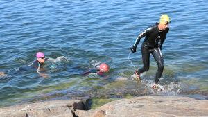En man iklädd våtdräkt tar sig upp ur havet längs med klippor. Två andra män väntar på sin tur.