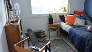 ett rum inrett med enbart begagnade prylar. skateboards, fläkt, en gul lampa och en gammal matta finns till exempel i rummet.