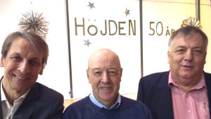 Tre glada män och i bakgrunden texten Höjden 50 år.