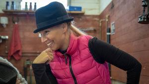 En ljushårig dam har en hatt på huvudet och ler.