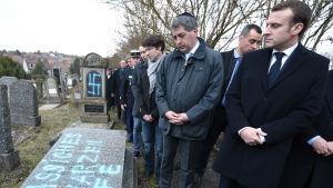 En bild på president Macron vid en gravgård i Frankrike som har vandaliserats.