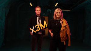 På vänster sida står Simon Karslsson med en gul x3m-skyllt i handen. Brevid, till höger står Märta Westerlund. Rummet är mörkt och ljuset skifar från magenta till gult.