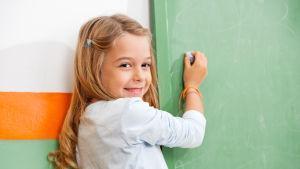 En flicka skriver med krita på en tavla.