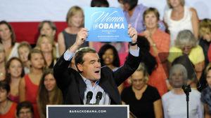 Mixahel Bennet i talarstolen på valmöte med skylt: Kvinnor för Obama, år 2012