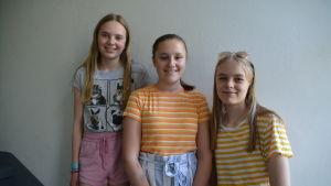 Tre flickor står på rad och ler