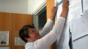 En kvinna hänger upp ett papper på en anslagstavla.