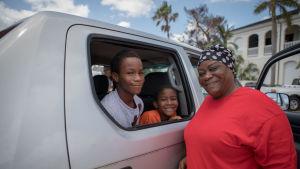 En kvinna till höger och två barn till vänster i bilen.