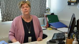 Kvinna i ljusröd kofta sitter vid sitt skrivbord och tänker.