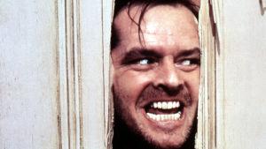 Närbild på Jack Torrance (Jack Nicholson) då han med yxa huggit ett hål i en dörr och nu med ett galet leende tittar in genom hålet.