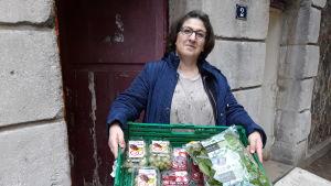 """Khadija Zoukou på välgörenhetsorganisationen La Main de l'Autre """"Din nästas hand"""" bär ut en låda full av mat."""