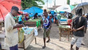 En kvinna med Bougainflagga på skjortan på torget i Bougainvilles huvudstad Buka