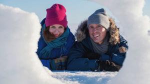 Egenlandin ohjelmajuontajat Nicke Aldén ja Hannamari Hoikkala kurkkaavat lumen takaa Hailuodossa.