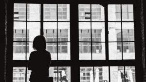 Naisen hahmo ikkunan edessä. Ikkunasta näkyy suljettuja aurinkovarjoja ja vatapäinen rakennus.