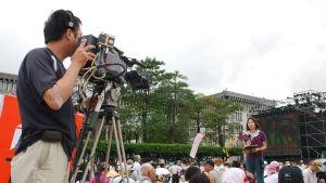 En kameraman filmar en journalist som står i en folkmassa med en mikofon.