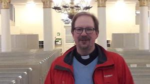 Rune Lindblom, präst i Korsholms svenska församling i Korsholmskyrka iklädd en röd jacka och prästkrage.
