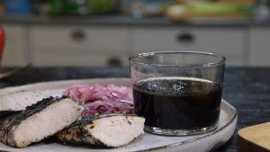 Hiillostetulla purjosipulilla maustettu grilliöljy lasissa pöydällä