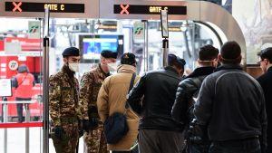 Soldater kontrollerade presumtiva passagerare på järnvägsstationen i Milano på måndagen.