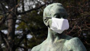En staty som föreställer en människa har fått ett munskydd över näsa och mun.