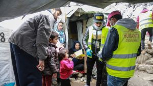 Hjälparbetare delar ut ansiktsmasker till en flyktingfamilj.