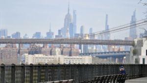 En ensam man blickar ut över Manhattan i ett coronadrabbat New york.