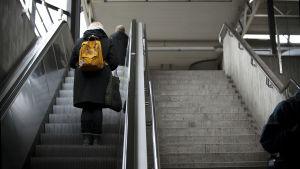 Personer står i rulltrappan med ryggen vänd mot kameran på en metrostation i Helsingfors.