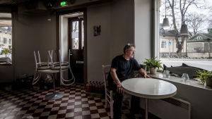 En man sitter vid ett tomt cafébord