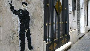 En satirisk väggmålning av Nordkoreas ledare Kim Jong-Un utanför en begravningsbyrå i rom