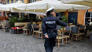 Kvinnlig polis övervakar avståndet mellan restaurangstolar i Nyhavn