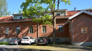 Johan Gadolins laboratorium, en rödmålad stenbyggnad med bilar parkerade framför.