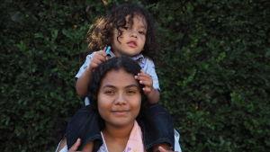 Kvinna bär liten pojke på sina axlar.