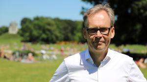 IT-företagaren Kaj Arnö står framför en massa människor som njuter av sommardagen i Englischer Garten i München