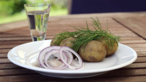En vit tallrik med några potatisar, ett knippe dill och några bitar sill med lök står på ett utebord i trä. Ett glas med klar vätska står bakom tallriken.