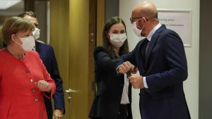 Sanna Marin armbågshälsar med Charles Michel. Tysklands förbundskansler Angela Merkel tittar på från sidan. Alla är iklädda munskydd.