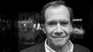 Svartvit porträttbild på Robert Paulig som ler rakt in i kameran.