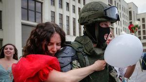 En demonstrant kramar en kravallpolis.