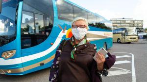 En kvinna bredvid en buss.